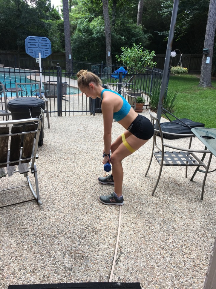 using the yellow moderate resistance band above the knees to perform weighted deadlifts at home