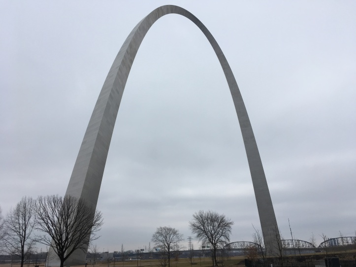 gateway arch in St. Louis Missouri takes up majority of the screen, set against a cloudy gay sky the silver arch is the focal point of this image